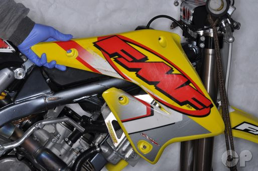 Remove the radiator shroud on the RMZ250 motorcycle.