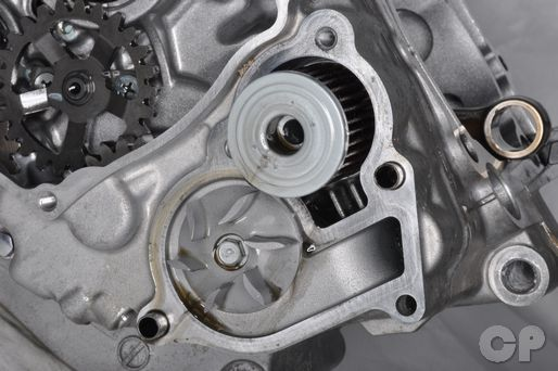 Remove the water pump cover on the Suzuki RM-Z250 to access the oil filter.