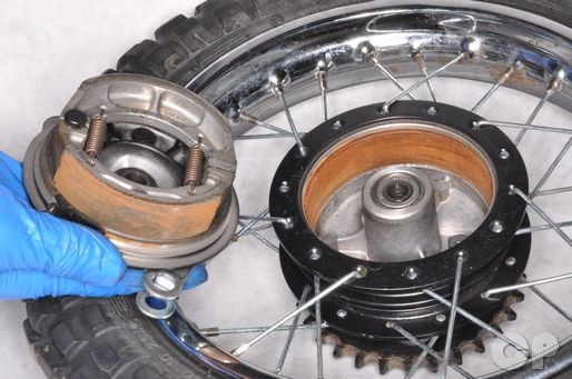 Remove the rear brake panel from the wheel to replace the shoes.