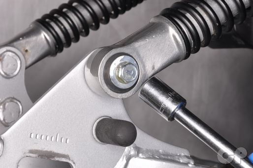 Tighten the lower shock absorber mounting bolt to specification.