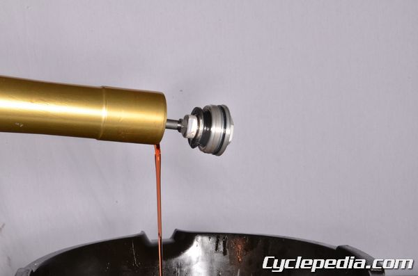 Turn the fork leg upside down to drain the fork oil into a suitable container